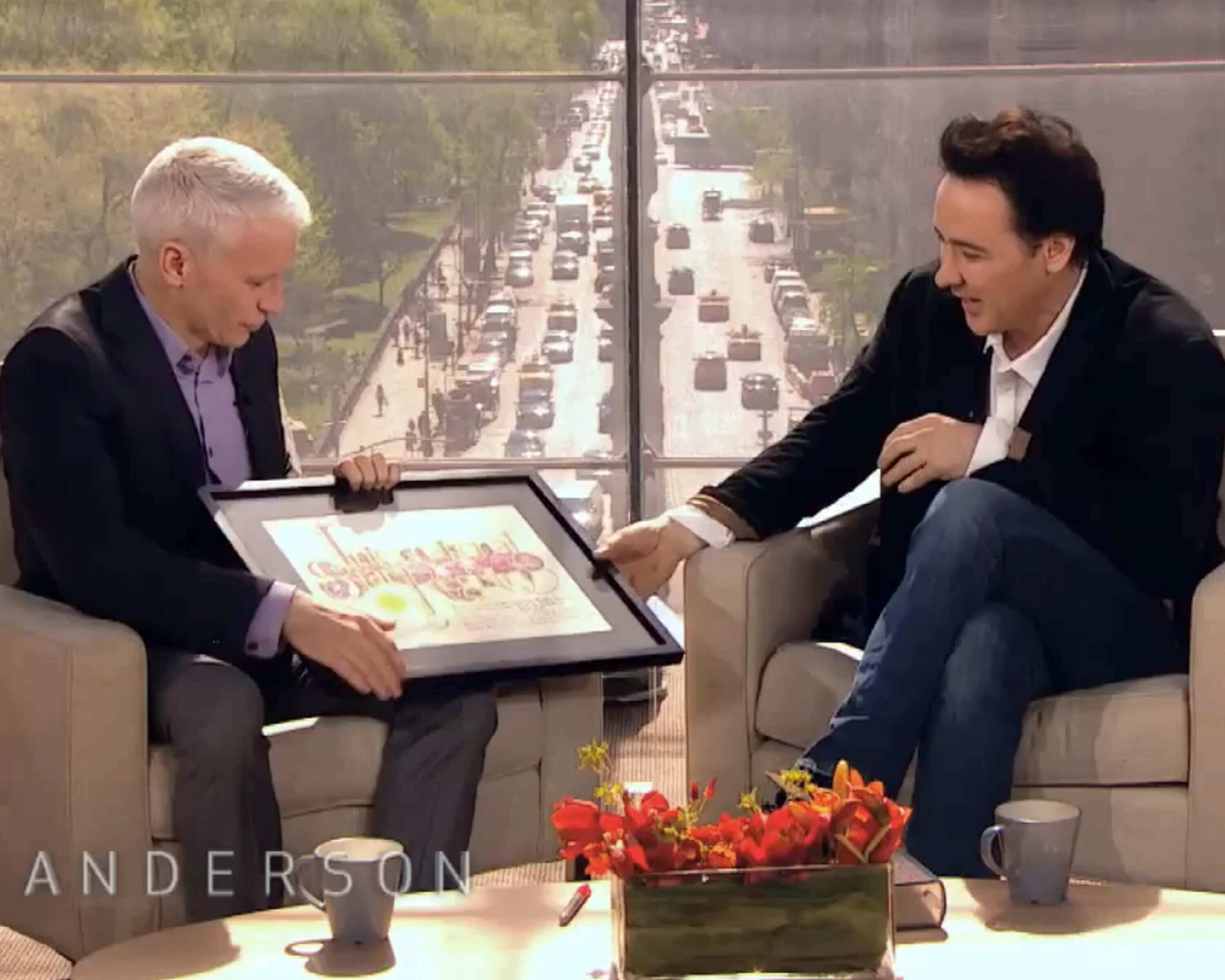 Celebrity television host Anderson Cooper presented movie actor John Cusack with a star gift from International Star Registry